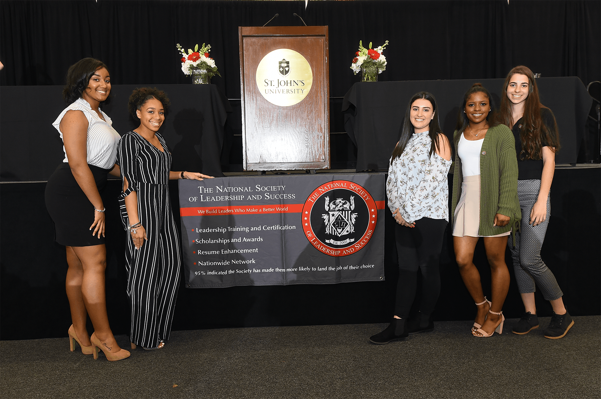 NSLS students posing in front of a banner