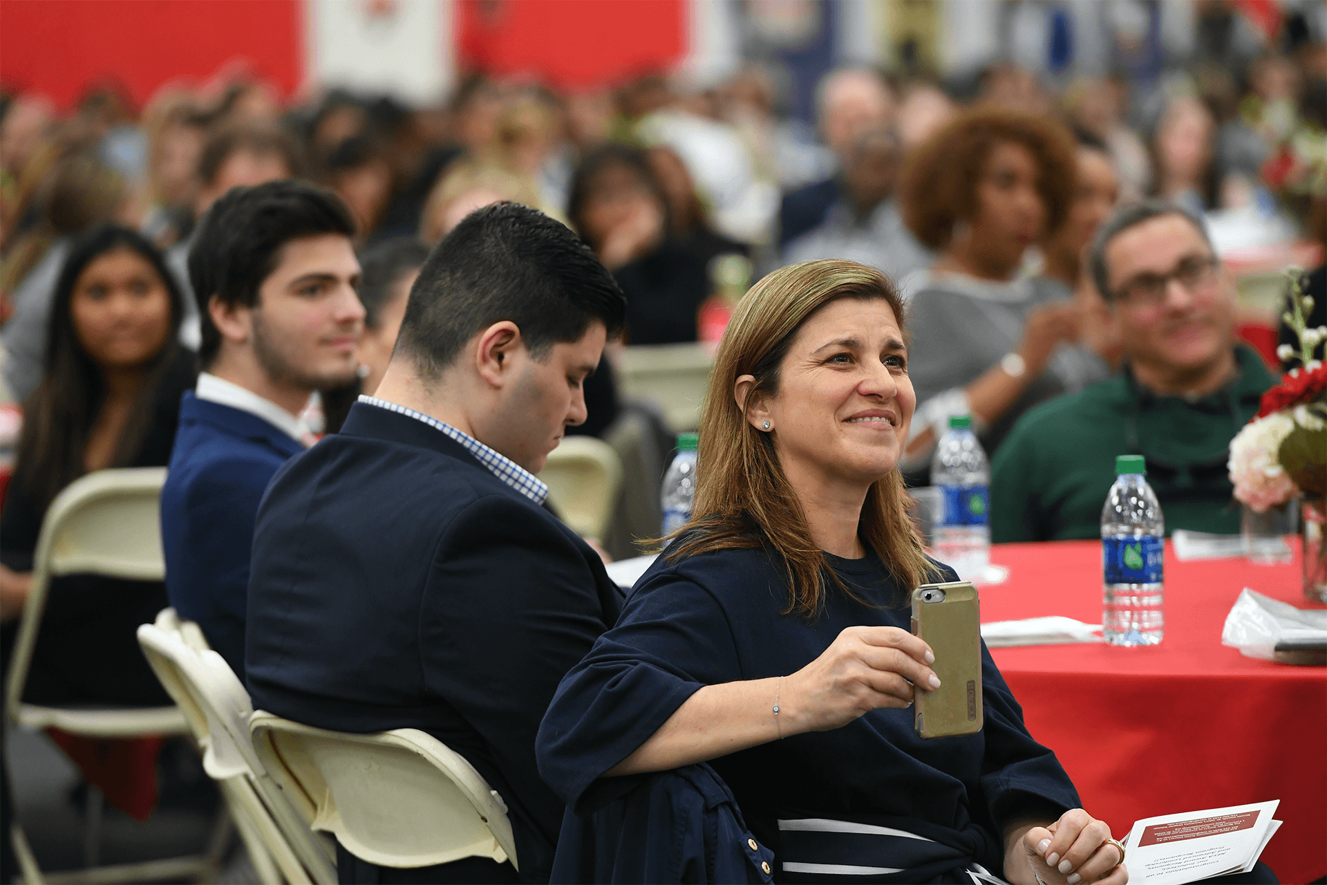 NSLS member smiling with a phone in her hand at an event