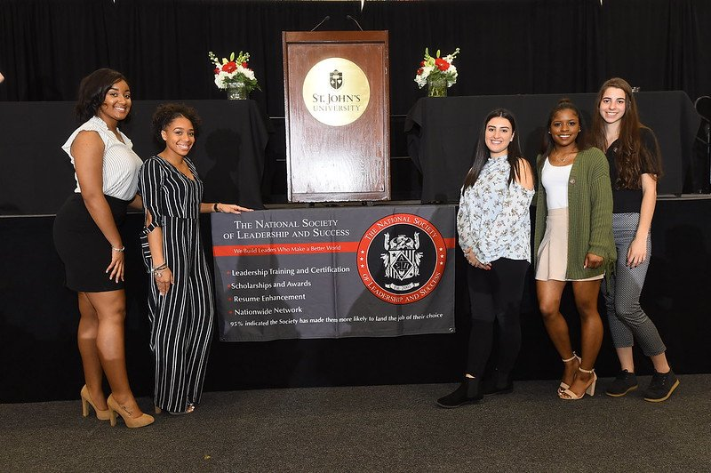 NSLS students posing for a photo in front of an NSLS banner