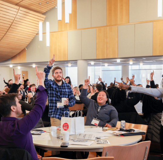Group of NSLS students holding up one finger around tables at an event