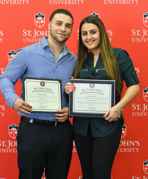 Two NSLS students posing with their diplomas